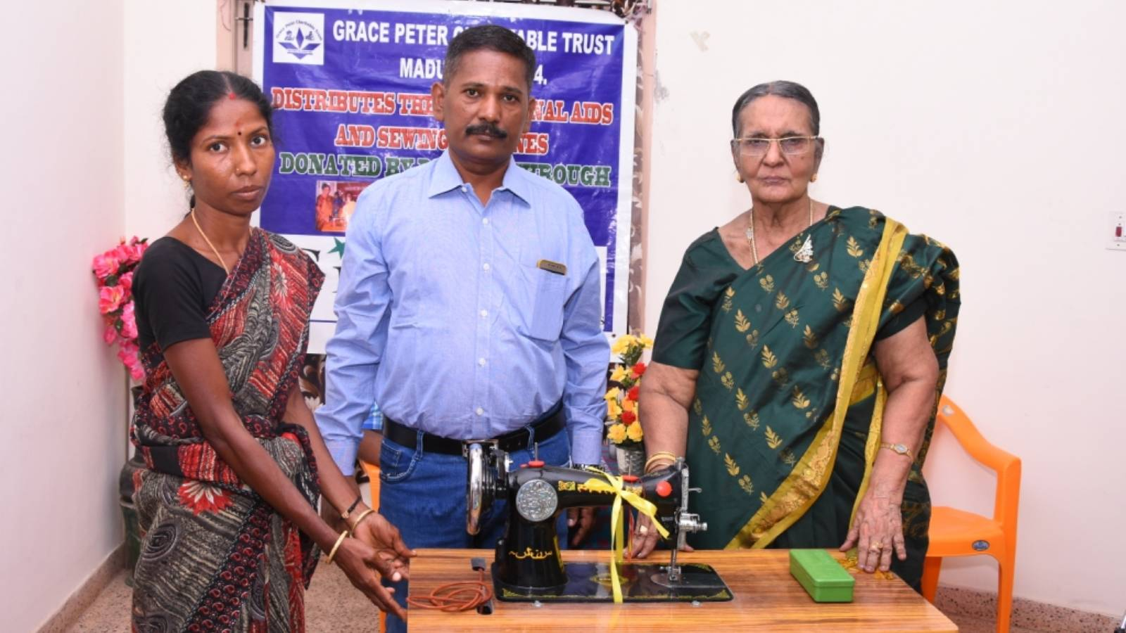 A Woman Beneficiary is receiving a Sewing Machine